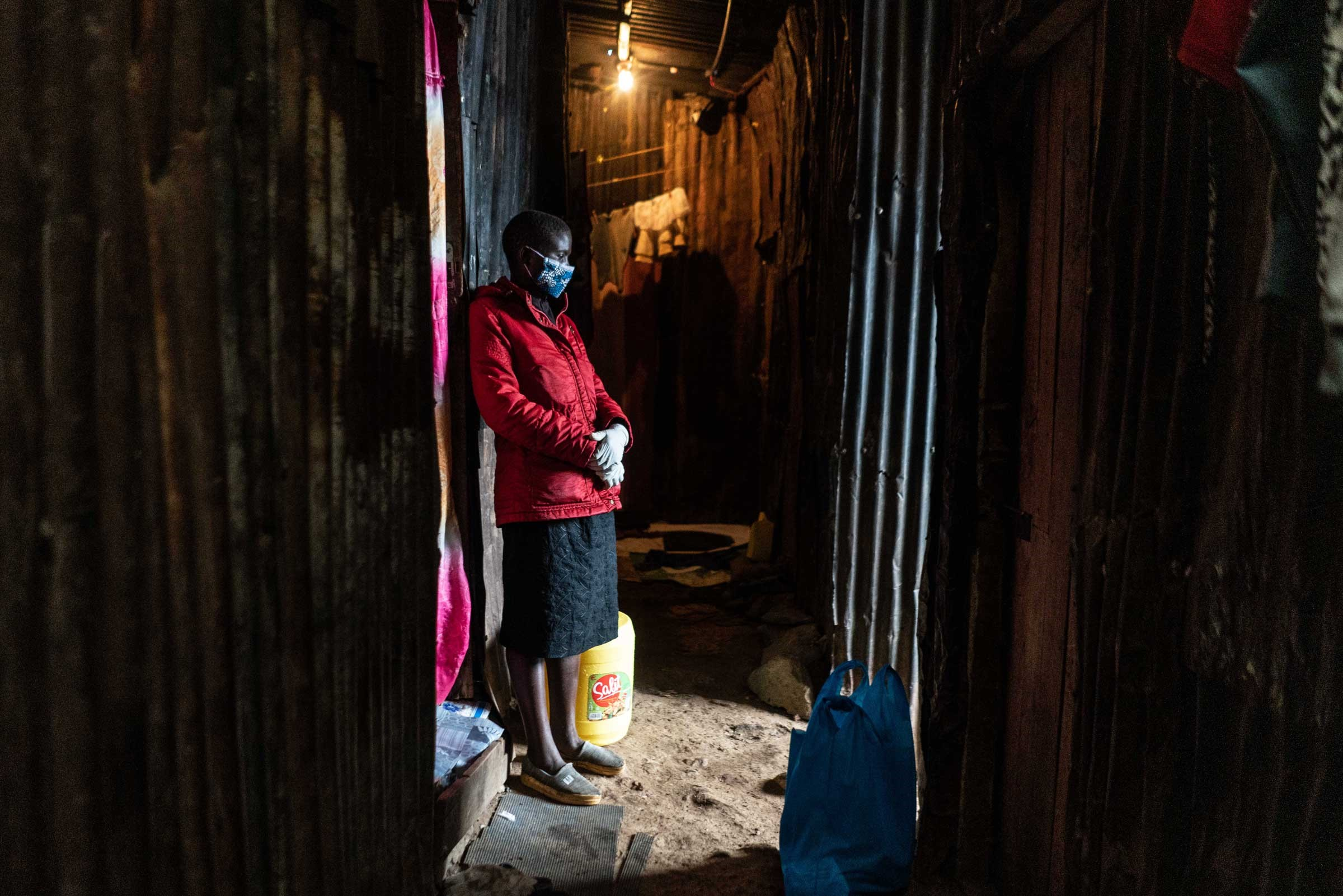 A Kenyan woman wearing a mask stands in a hallway waiting for food rations.