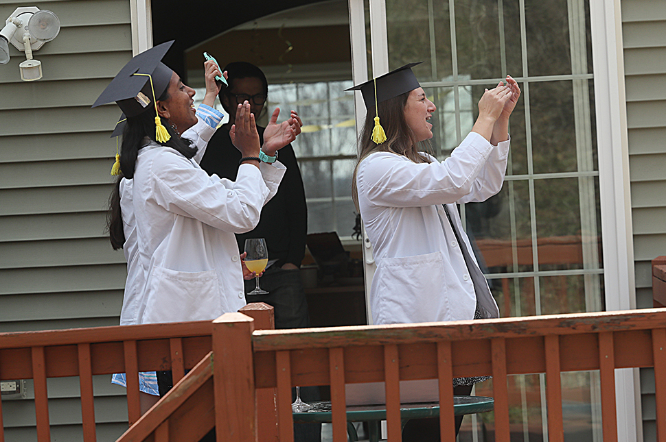 Three women wearing white graduation gowns and black graduation caps with yellow tassels stand on a porch and applaud.