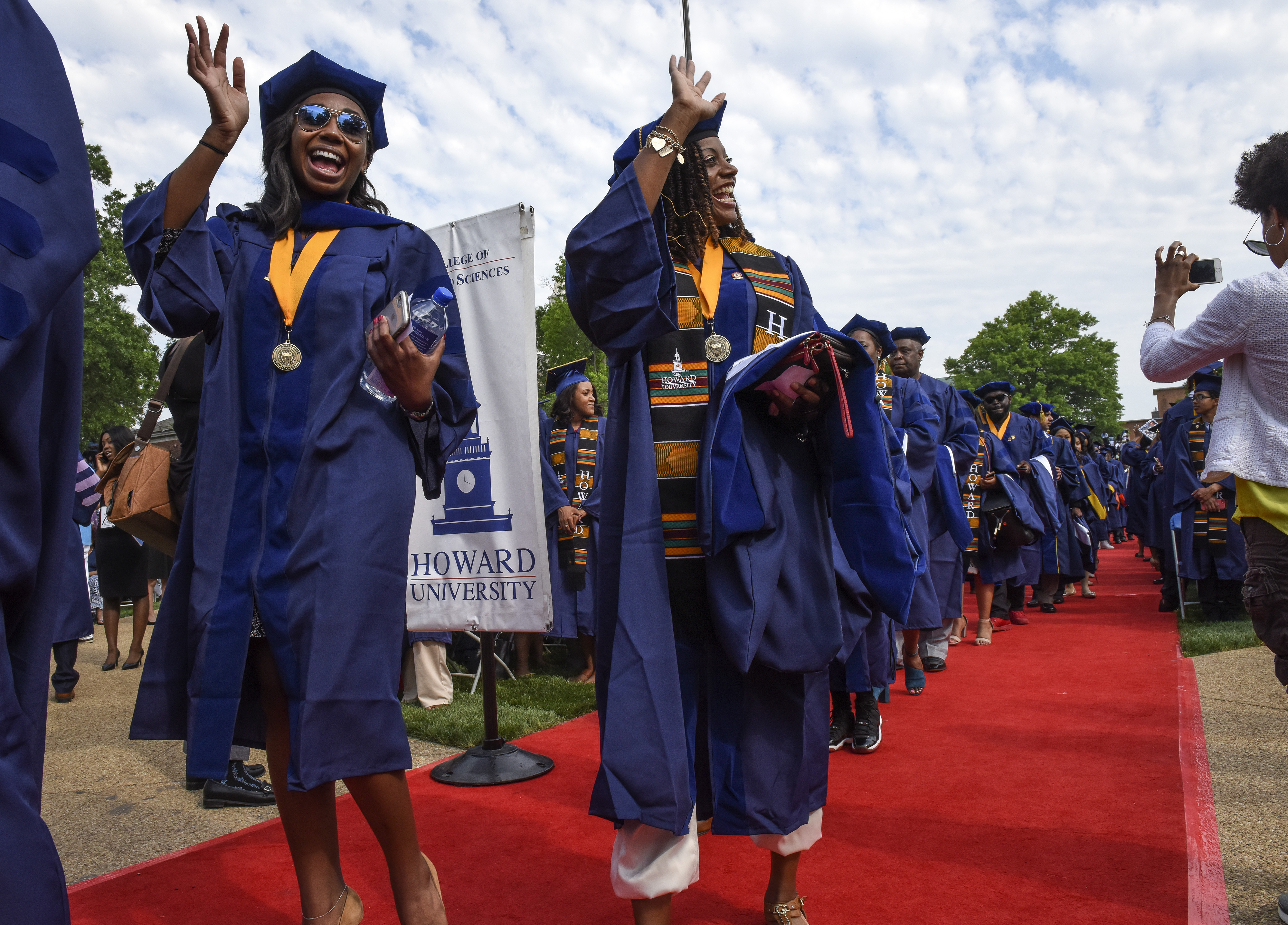 Medical students at Howard University wave as they parade in during commencement ceremonies