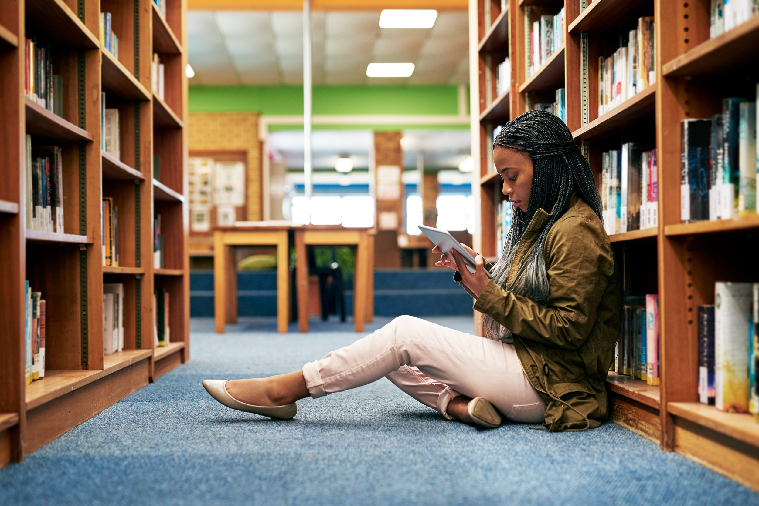 A black student sits between shelves at a campus library reading on a tablet
