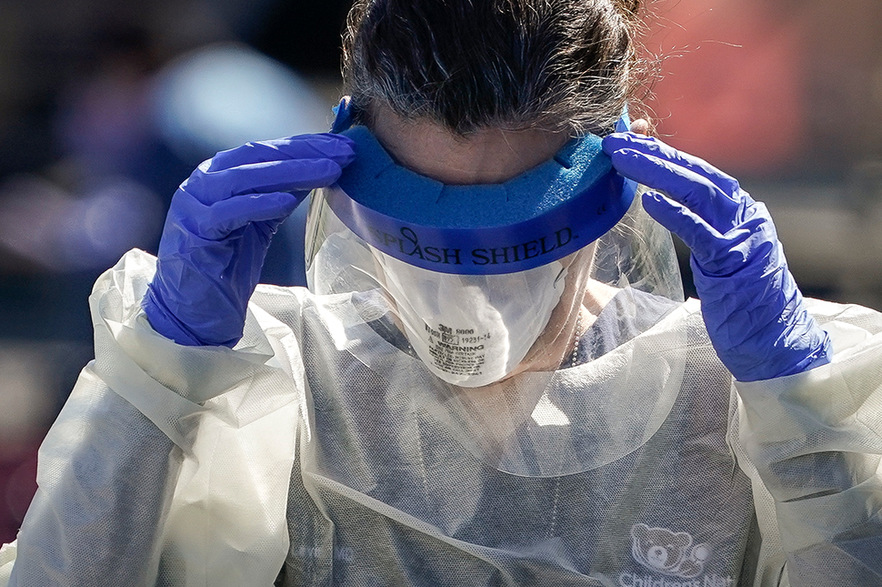 A healthcare worker wearing a yellow gown and blue gloves holds her hands up to her temples to adjust her personal protective face shield at a drive-thru coronavirus testing center