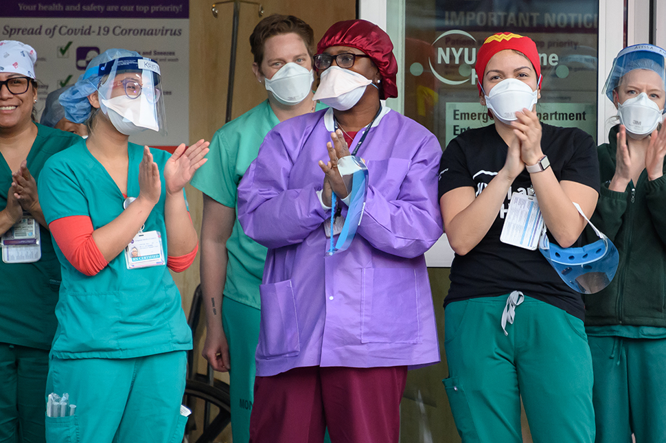 A group of nurses wearing scrubs, protective face masks, and hair nets stand outside applauding other essential staff and healthworkers