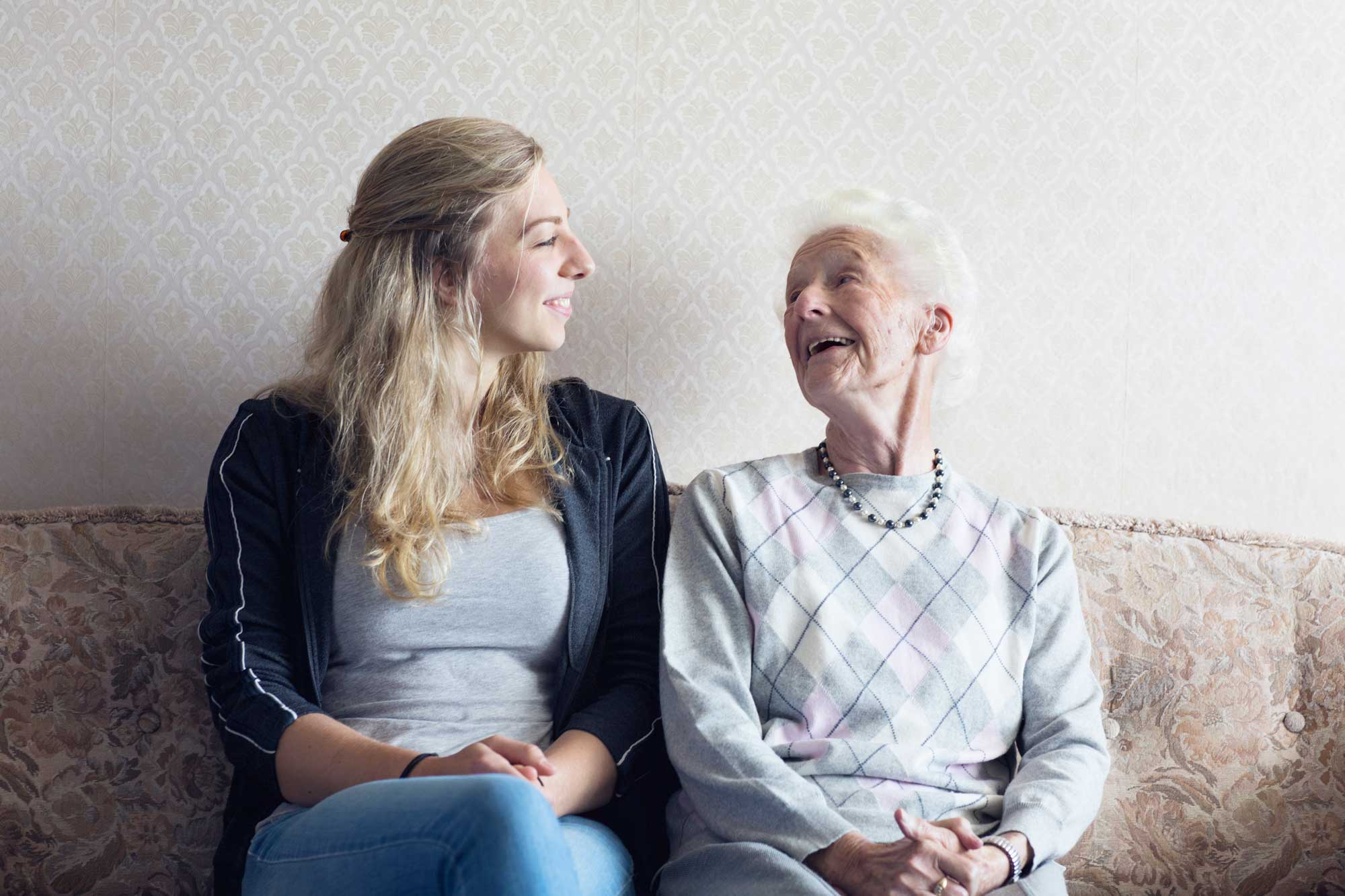 A young woman sits on a couch next to an elderly woman. The two are looking toward each other and smiling.