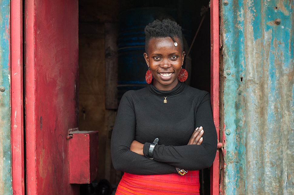 Ann Mitu stands in a doorway with her arms crossed