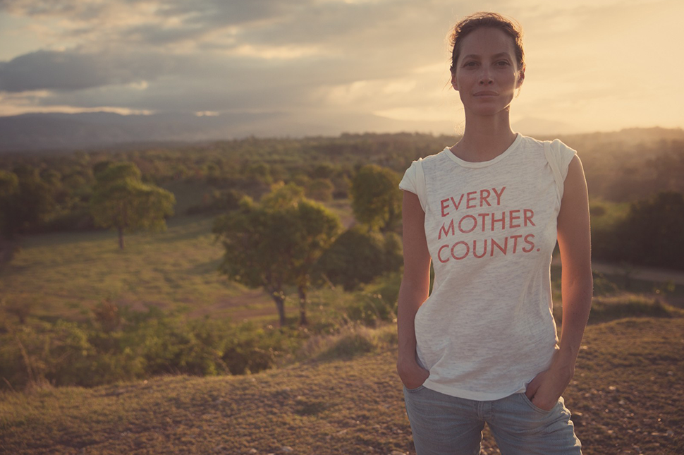 """Christy Turlington Burns stands in a field wearing a shirt that reads """"every woman counts."""""""