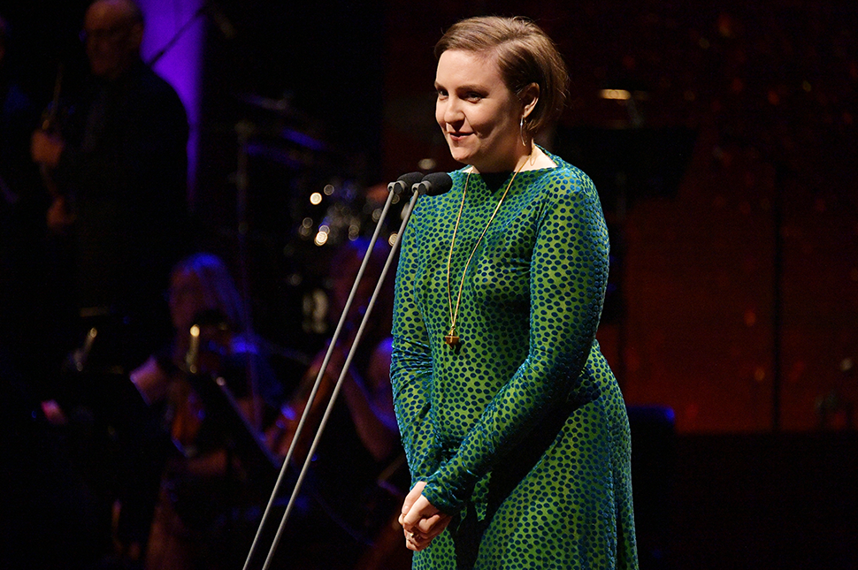 Lena Dunham standing on stage at an event