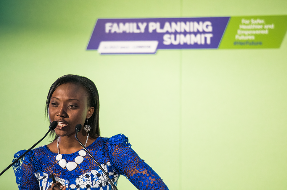 Margaret Bolaji sits at a table and speaks into a microphone at the Family Planning Summit.