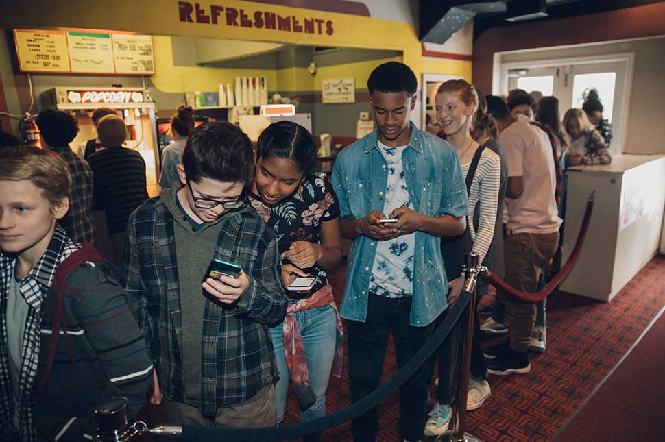 Kids staring at their phones while standing in line for a movie