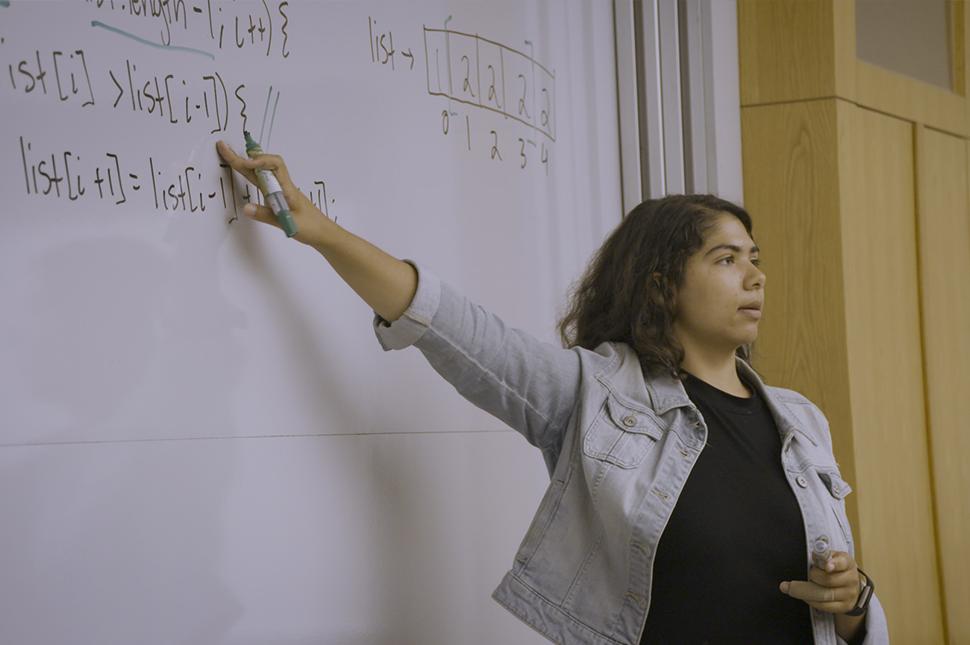 A University of Washington student motions to a whiteboard where she has written programming language
