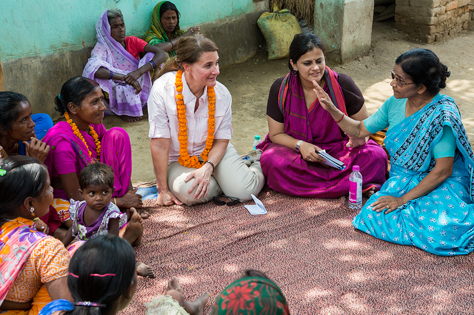 Melinda Gates sits on the floor discussing with women in India.