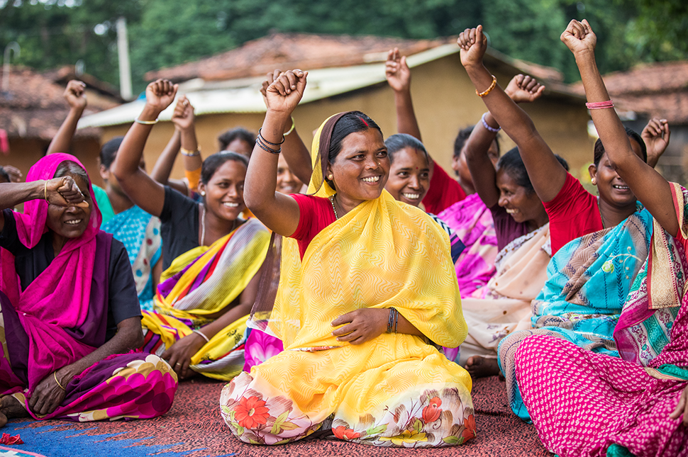 Women in India sit cross-legged with fists raised in unity. | Mansi Midha | Gates Archive
