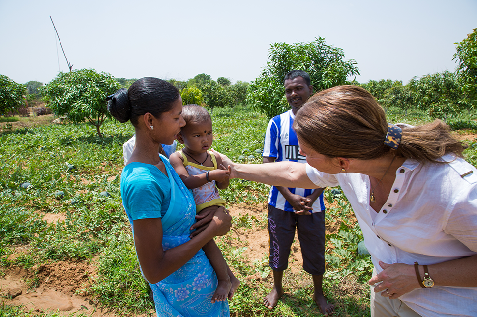 Melinda Gates interacting with a woman and her baby with a rural farm in the background.