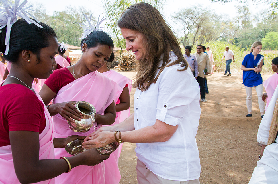 Two women pouring water over Melinda Gates' hands