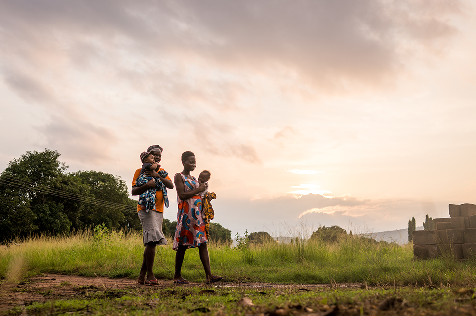 Two women in Ghana carry their children as they walk along a path at sunset.