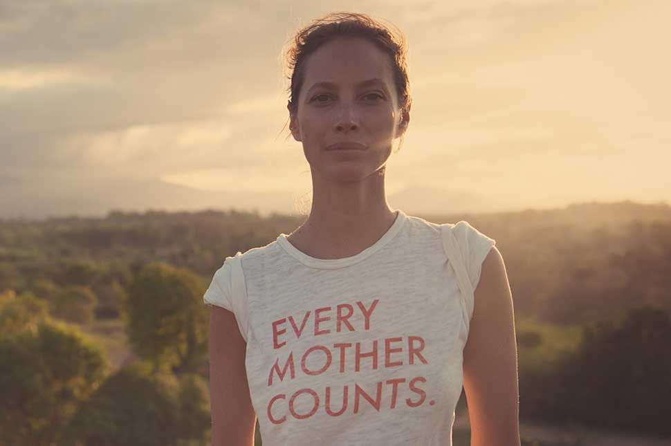 Portrait of Christy Turlington Burns standing with a sunset behind her while wearing an Every Mother Counts T-Shirt