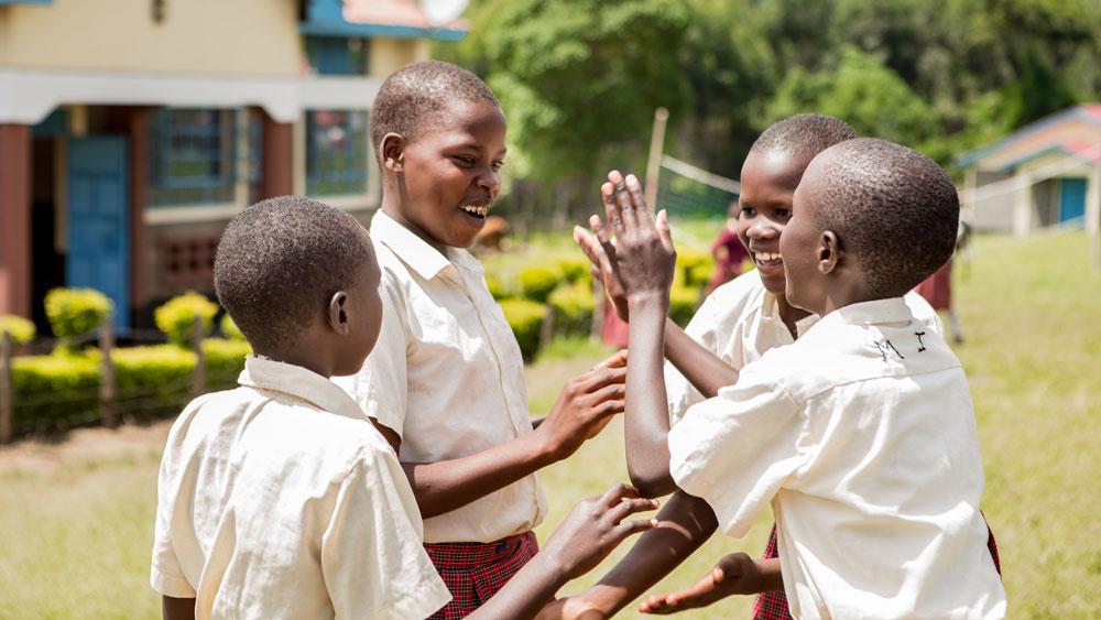Girls in Kenya wearing school uniforms play patty cake