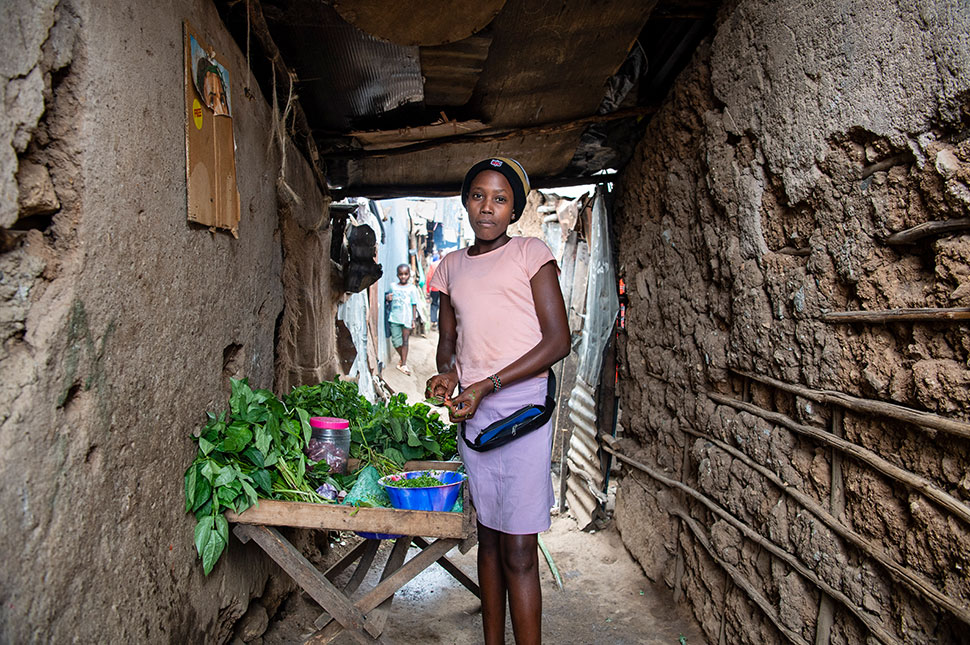 A young girl in Kenya stands in an informal market selling vegetables while out of school due to the COVID-19 pandemic