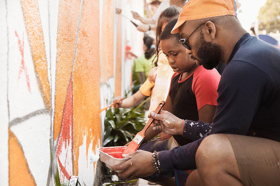 A black man helps a young black boy paint a mural on a wall at a community center