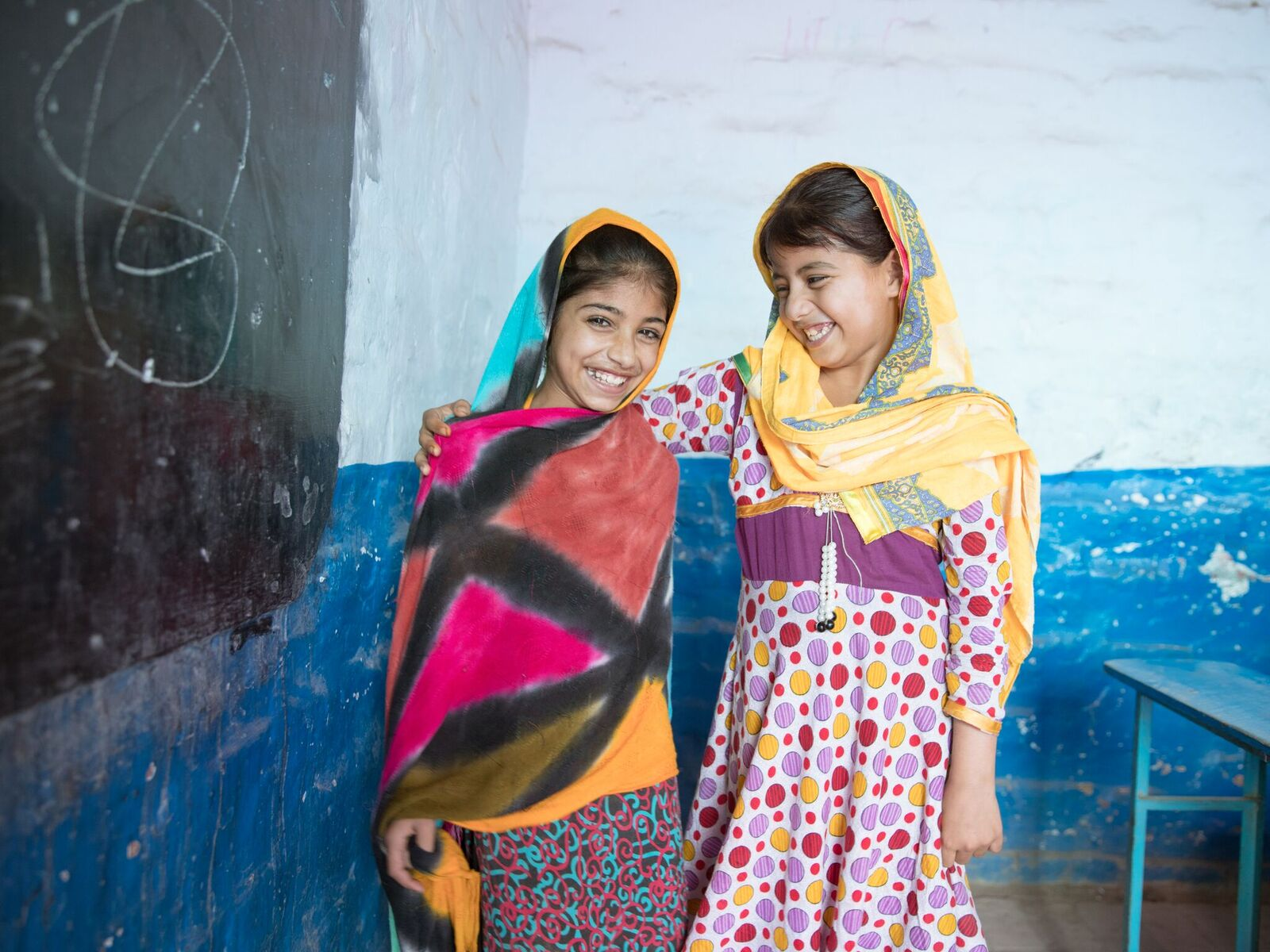 Two young girls wear colorful dresses and head scarfs in a classroom. They are smiling and have their arms around each other.