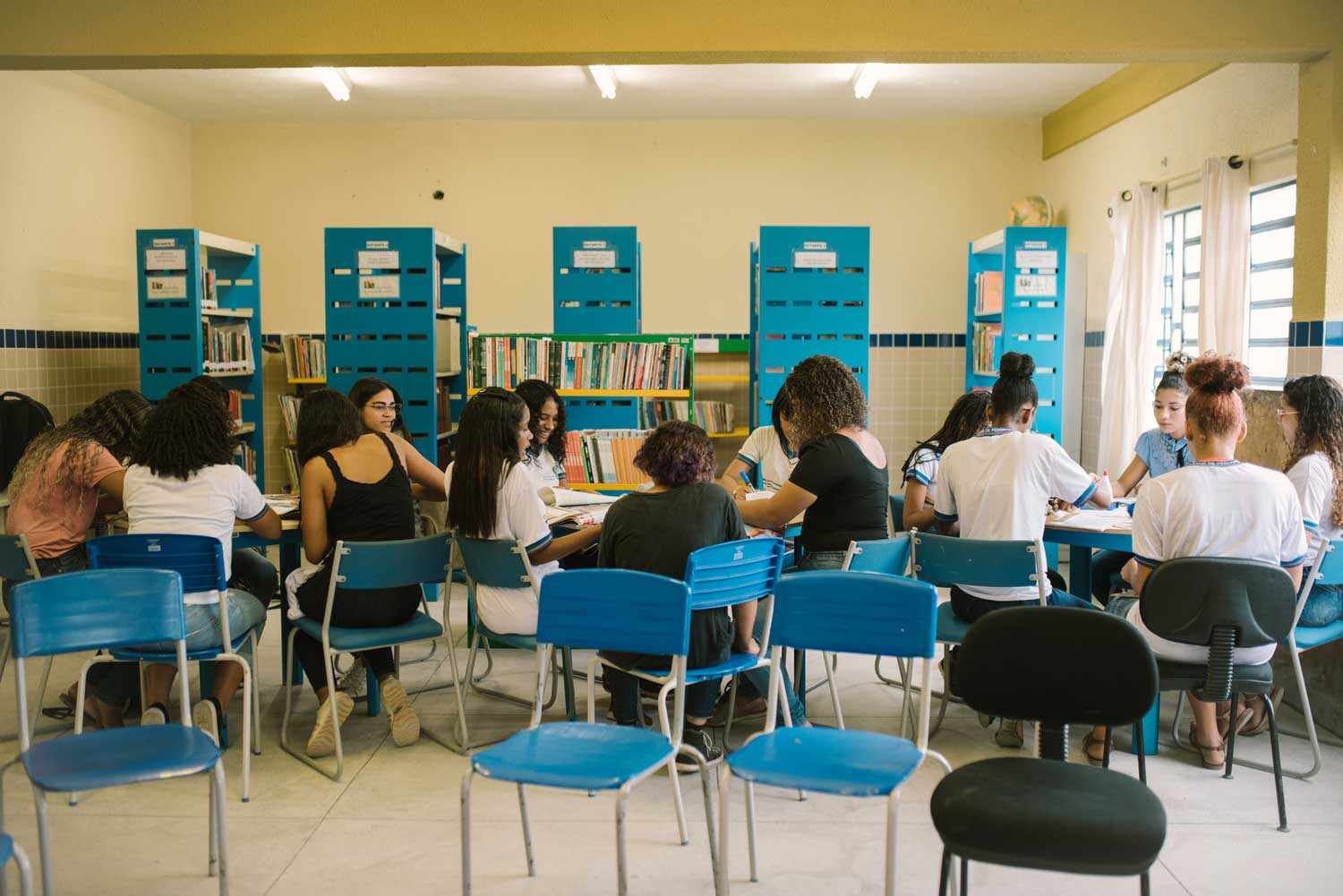 Young women sit in a classroom in groups on blue chairs.