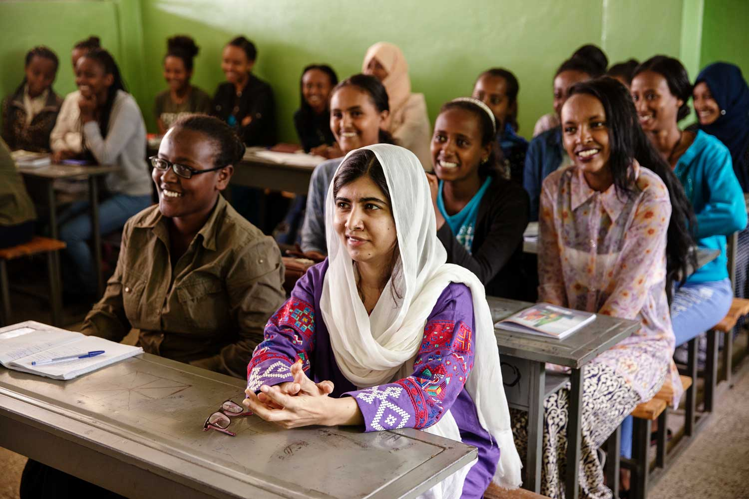 Malala sits at a classroom desk among a group of young women in an Ethiopian classroom.