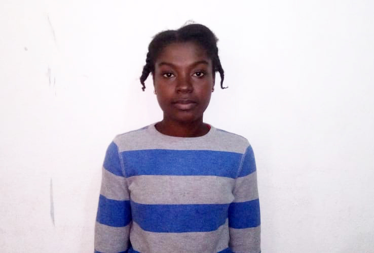 A young girl in Mozambique stands for a picture in front of a white wall while wearing a blue and grey striped sweater