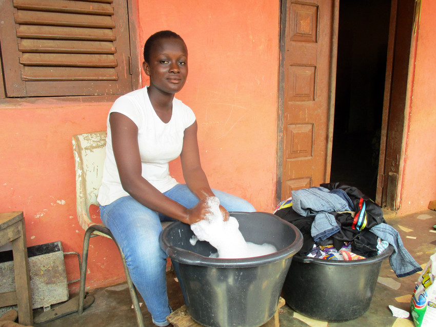 A young girl in Ghana sits in a chair in front of a building scrubbing laundry in a bucket. A full bucket of laundry sits next to her.