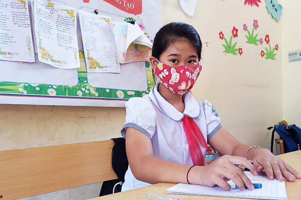 A young girl sits in a classroom in Vietnam. She wears a mask while she works on her schoolwork.