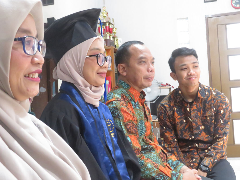 A young woman in Indonesia wears a graduation cap and gown while sitting with her family watching a screen.