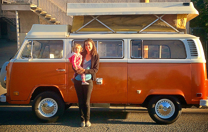 Courtney Martin stands in front of an old Volkswagen bus holding her daughter