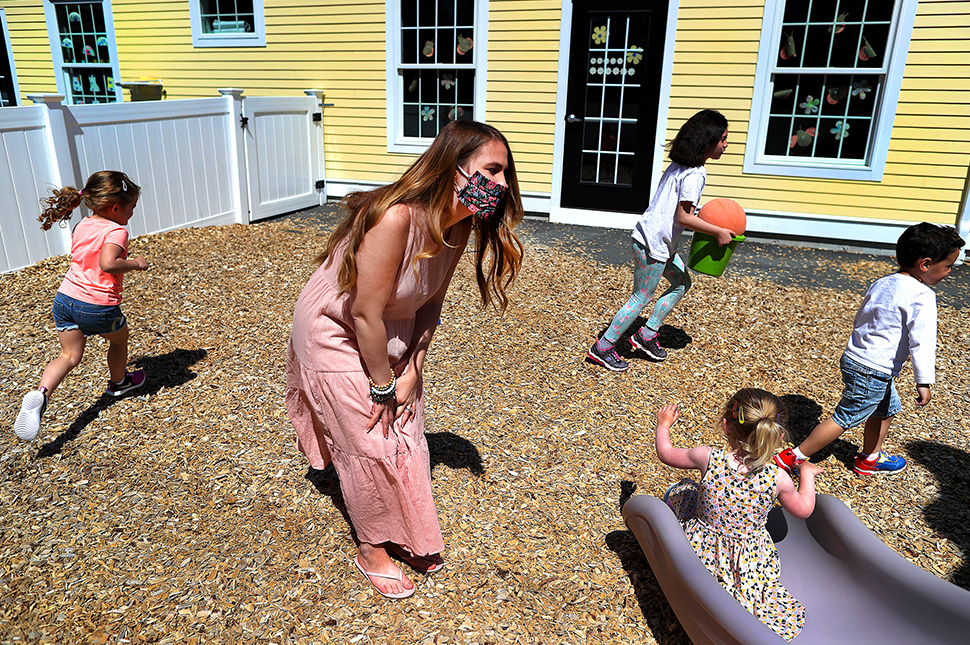 A daycare worker leans over and watches a child go down a slide with other children running around behind her.