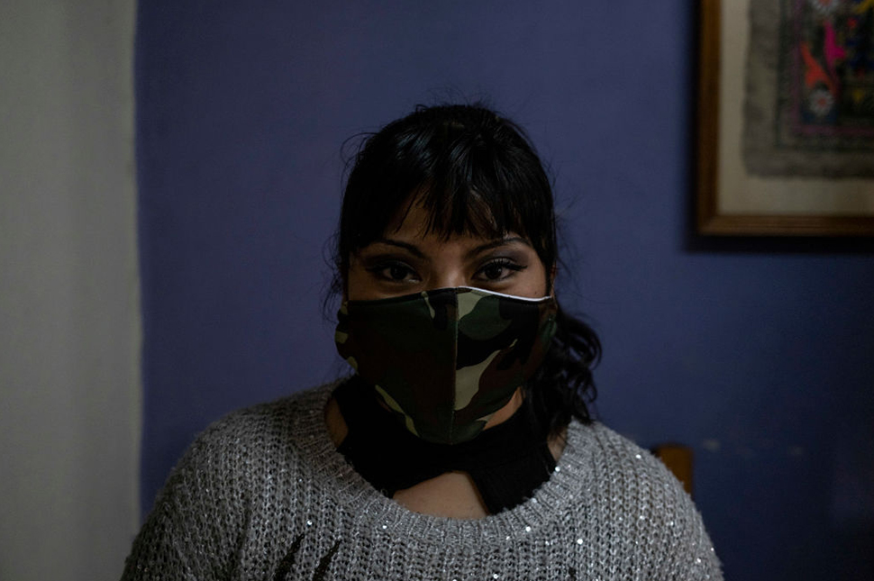 A woman wearing a camouflaged mask poses for a portrait in front of a purple wall. Domestic Violence Cases Surge In Mexico City As Result Of Families Quarantining : News Photo