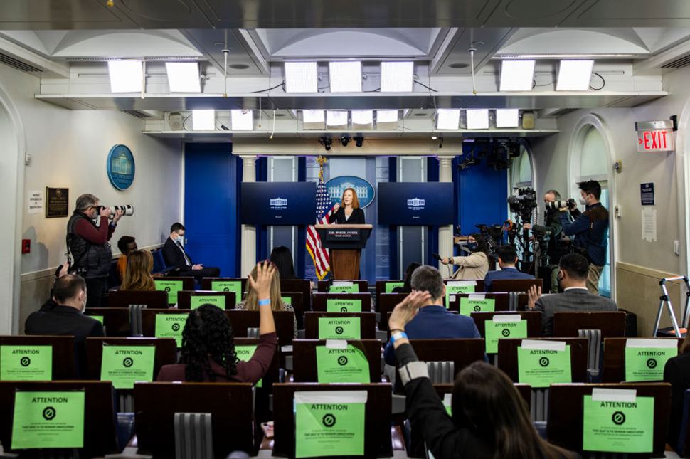 A photo from behind two women sitting in the white house press pool raise their hands to ask a question of a Jen Psaki, the White House Press secretary, who stands at the podium.