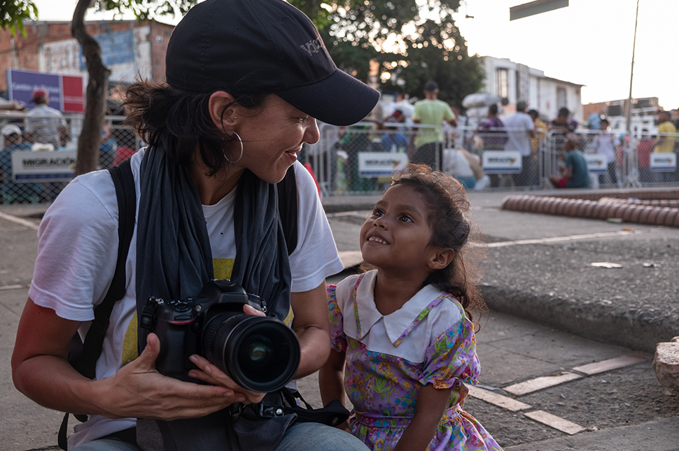 A woman holding a camera crouches down to smile at a young girl who is looking up toward her, smiling back. They are in the street and behind them are fences with a crowd standing on the other side.
