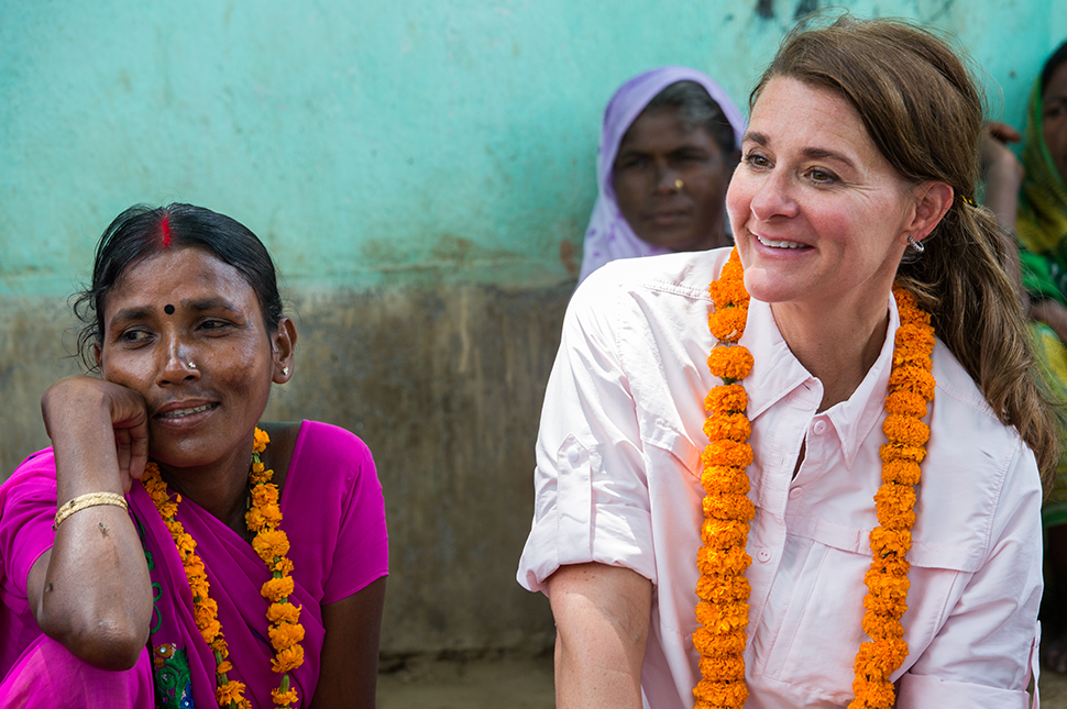 Melinda Gates sits and talks in a group.